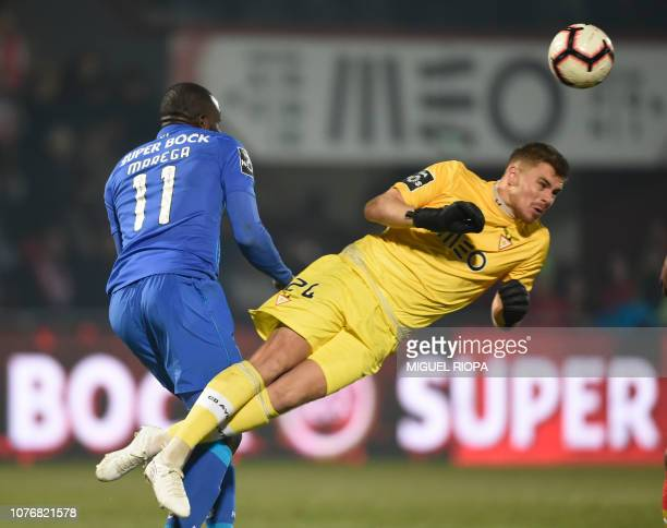 CD Aves' French goalkeeper Quentin Beunardeau heads the ball beside Porto's Malian forward Moussa Marega during the Portuguese League football match...