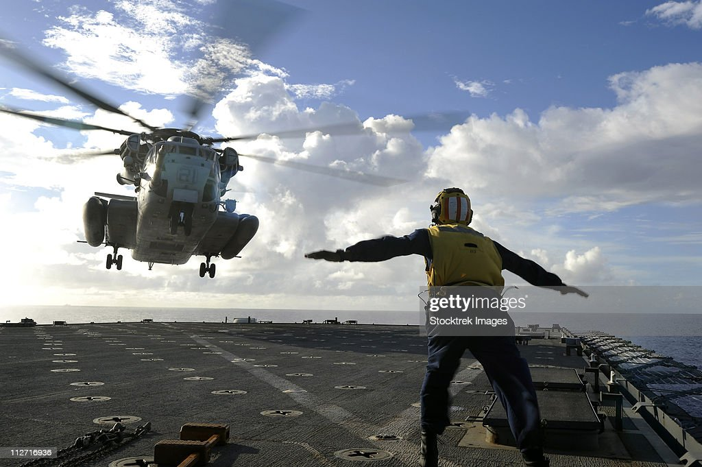Aviation Boatswain's Mate directs a CH-53E Super Stallion onto the flight deck of USS Harpers Ferry. : Stock Photo
