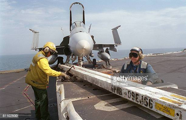 """Aviation Boatswains Mate First Class Ivan Borja And Airman Doug SchaeferStow The Tow Bar After Moving A F/A 18 """"Hornet"""" Strike Fighter. The USS Carl..."""