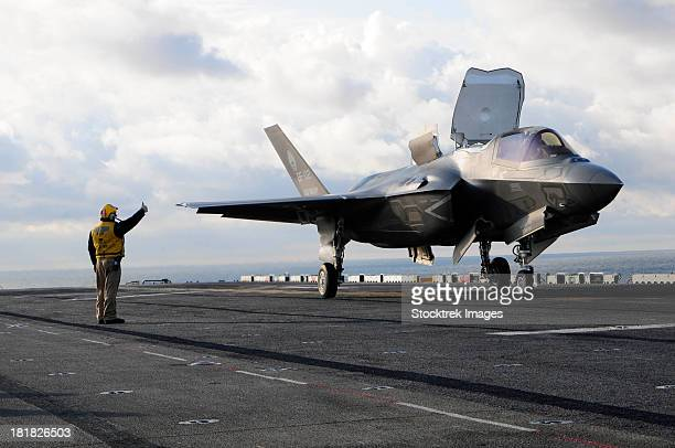 Aviation Boatswain's Mate signals the pilot to lift an F-35B Lightning II off the flight deck.