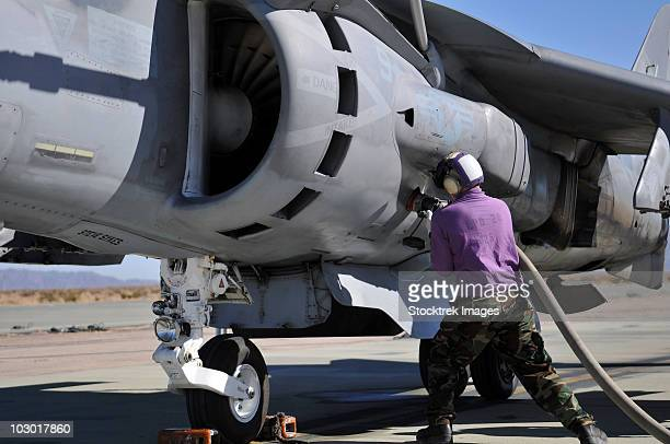 aviation fuel technician attaches a fuel line to an av-8b harrier. - refuelling stock pictures, royalty-free photos & images