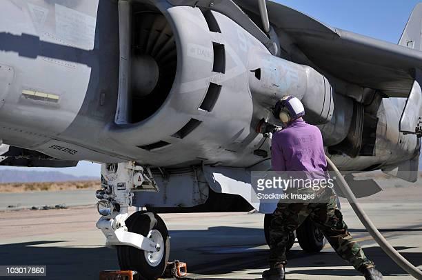 Aviation fuel technician attaches a fuel line to an AV-8B Harrier.