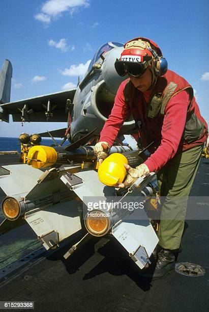 Aviation Ordnanceman 1st Class Michael Gettys removes the cover from the tip of an AIM9 Sidewinder missile prior to loading the ordnance on an A7E...