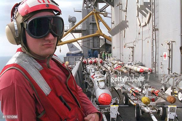 "Aviation Ordnanceman Second Class Ricardo Salicrup From Santurce, P.R. Stands Watch Over The ""Bomb Farm"" On The Flight Deck February 27,1999. Carl..."