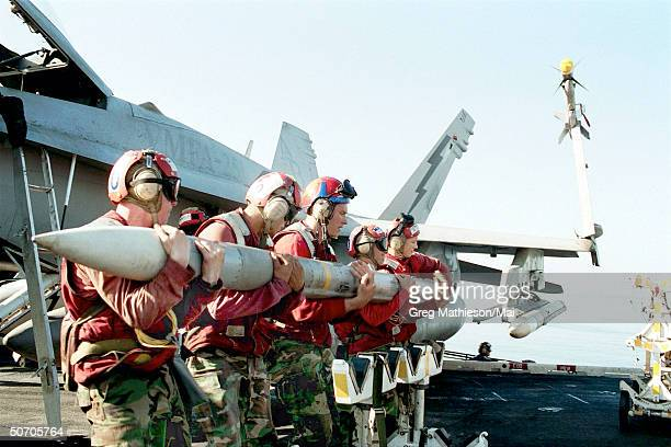 Aviation Ordnancemen loading an AIM120 Advanced MediumRange AirtoAir missile on the wing of an F/A18 Hornet strike fighter USS Theodore Roosevelt and...