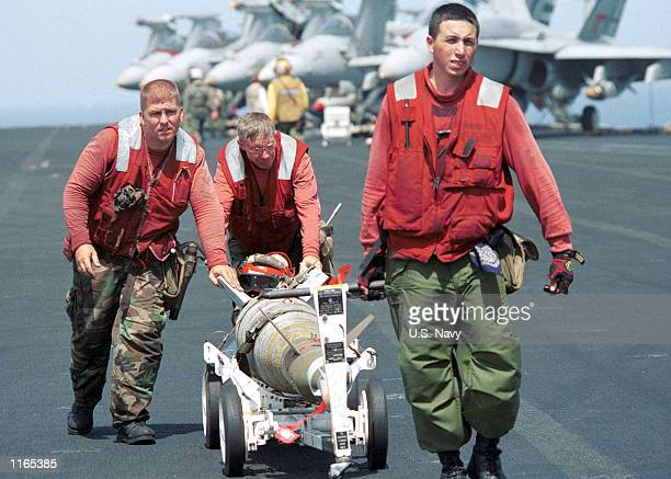 Aviation ordnancemen move a laser guided bomb across the flight deck in preparation for afternoon flight operations against military and terrorist...
