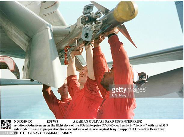 """Aviation Ordnancemen on the flight deck of the USS Enterprise load an F-14 """"Tomcat"""" with an AIM-9 sidewinder missile in preparation for a second wave..."""