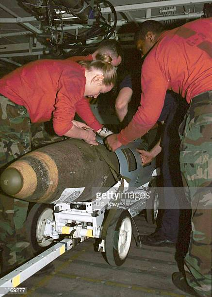 Aviation Ordnancemen secure an 84 type j-dam bomb for transfer from magazine storage to the flight deck October 8, 2001 onboard the USS Carl Vinson...