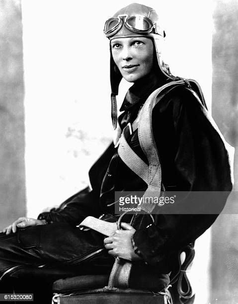 Aviator Amelia Earhart poses in her flight suit