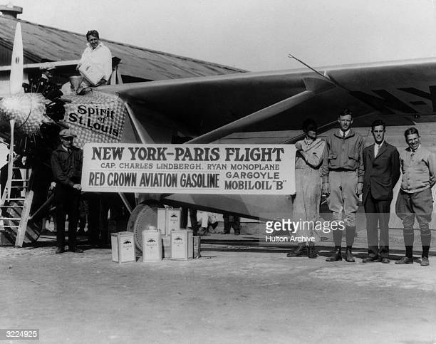 Aviator Charles Lindbergh poses next to the 'Spirit of St. Louis' in a promotional portrait for Red Crown Aviation Gasoline before taking off for a...