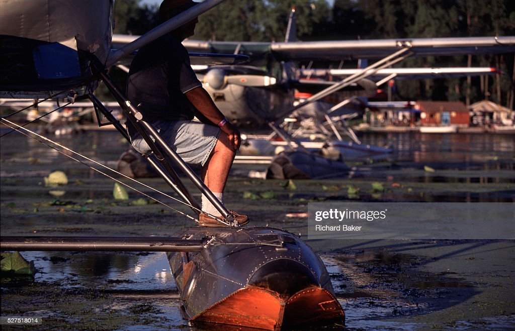 AN aviator sits on a float of his aircraft in a parking lake