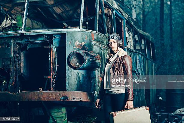 Aviator woman stands in front of a destroyed vehicle