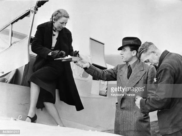 L'aviatrice Amy Johnson prenant une cigarette que lui tend son mari Jim Mollison avant son départ pour tenter de battre le record du LondresLe Cap à...