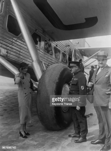 L'aviatrice anglaise Amy Johnson en conversation avec un agent parisien devant l'énorme roue du nouvel avion anglais 'Le Scylla' au Bourget France le...