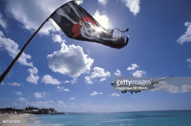 L'avion Boeing 747 de la compagnie Corsair atterrit a l'aeroport princesse Juliana survole la plage passe proximit d'un drapeau de pirate