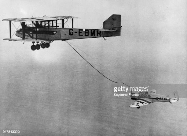 L'avion de Sir Alan Cobham est ravitaillé en plein vol lors d'un essai à l'aérodrome Ford au RoyaumeUni le 12 septembre 1934
