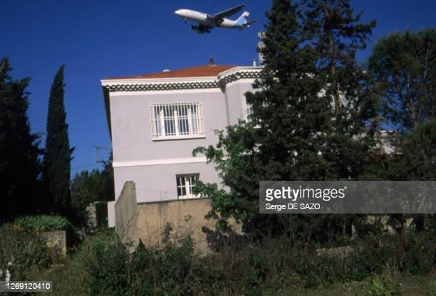 Avion passant au-dessus d'une zone résidentielle à Marignane, circa 1990, dans les Bouches-du-Rhône, France.