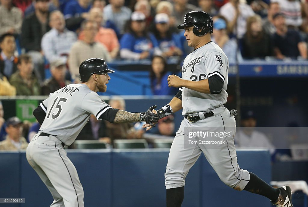 Avisail Garcia #26 of the Chicago White Sox is congratulated by Brett Lawrie #15 after scoring a run in the seventh inning during MLB game action against the Toronto Blue Jays on April 25, 2016 at Rogers Centre in Toronto, Ontario, Canada.