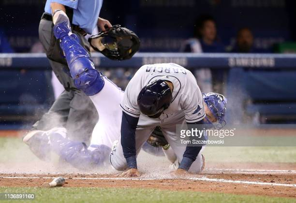 Avisail Garcia of the Tampa Bay Rays is tagged out at home plate by Luke Maile of the Toronto Blue Jays as he tries to score in the seventh inning...