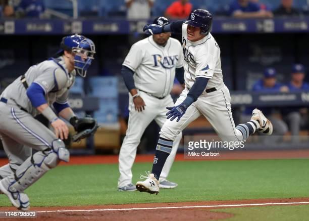 Avisail Garcia of the Tampa Bay Rays runs past Danny Jansen of the Toronto Blue Jays on his insidethepark home run in the third inning of a baseball...