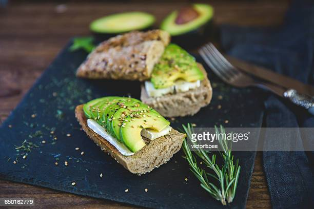 avocado and brie cheese sandwich on mixed seed roll - whole wheat stock pictures, royalty-free photos & images