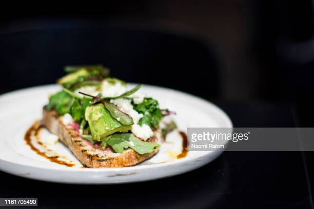 avocado and fetta cheese on toasted bread, served on a contemporary white plate, black background - avocado toast stockfoto's en -beelden