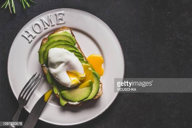 avocado and poached egg sandwich on plate with cutlery, copy space - avocado toast stockfoto's en -beelden