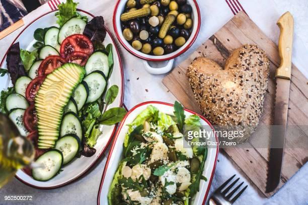 avocado and potato salads with grainy bread and olives - gekarteld stockfoto's en -beelden