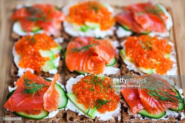 Avocado and red caviar, smoked salmon and cucumber rye crisp toasts, appetizer, close up