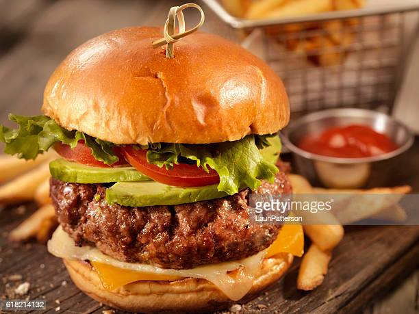 avocado cheeseburger with a basket of fries - hamburger stock pictures, royalty-free photos & images