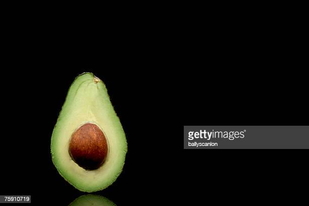 Avocado (persea americana) cut in half with seed on a black background