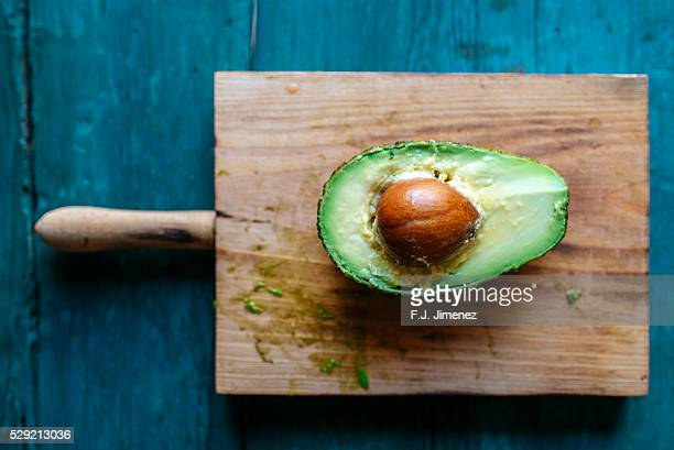 Avocado cut in the foreground on cutting board