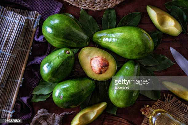 avocado fruits and sliced avocados on a wooden table - ripe stock pictures, royalty-free photos & images