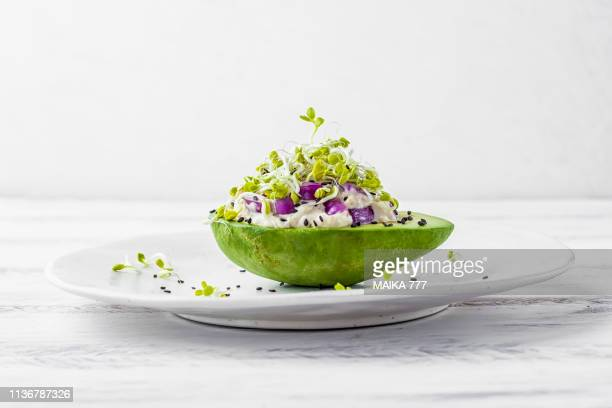 avocado garden stuffed with tuna, mayonnaise, red onion, black sesame seeds and radish sprouts - comida vegetariana fotografías e imágenes de stock