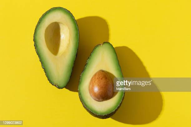avocado halves with trendy hard light and hard shadow on yellow background - ingredient stock pictures, royalty-free photos & images