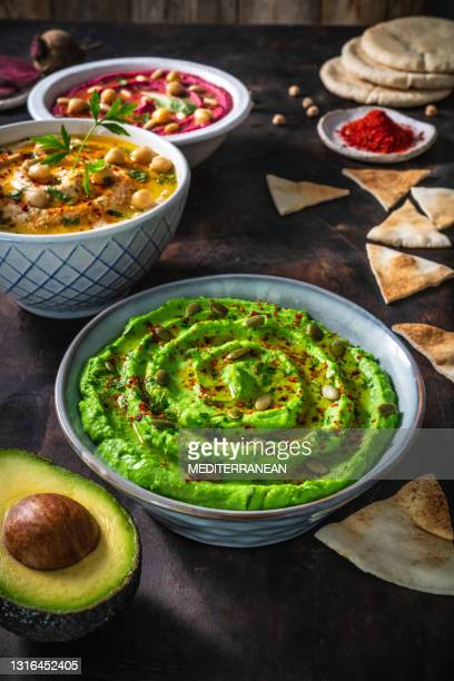 avocado hummus bowl closeup with pita flatbread dipping on dark wood background - lebanon country stock pictures, royalty-free photos & images