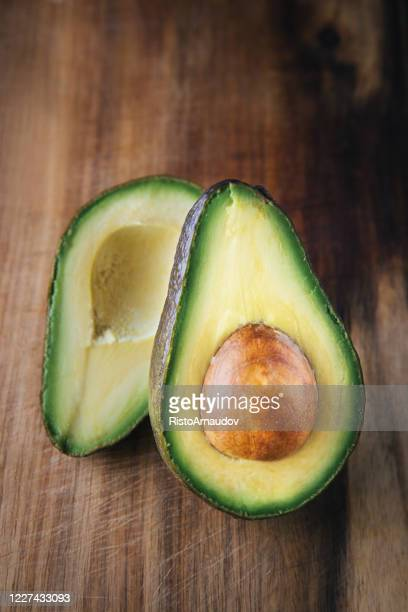 avocado on a wooden background - insignia stock pictures, royalty-free photos & images