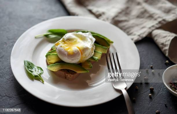 avocado on toast with poached egg - avocado toast stockfoto's en -beelden
