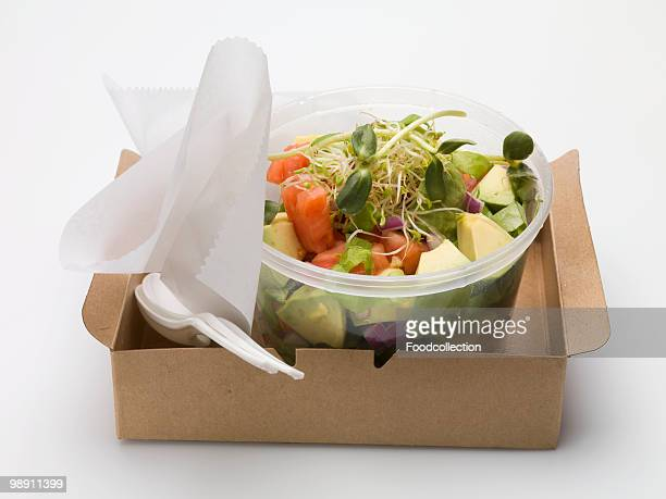 Avocado salad with sprouts in plastic container.
