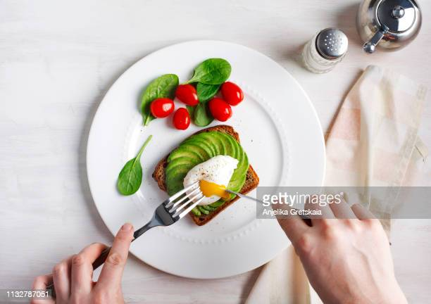 avocado sandwich with poached egg. sliced avocado and egg on toasted bread for healthy breakfast - avocado toast stockfoto's en -beelden