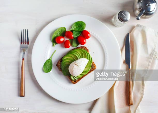 avocado sandwich with poached egg. sliced avocado and egg on toasted bread for healthy breakfast - repas servi photos et images de collection