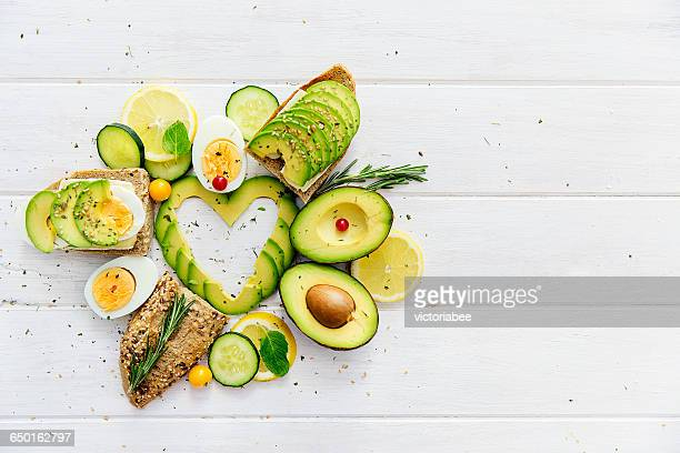 Avocado slices in heart shape with bread, lemon and egg