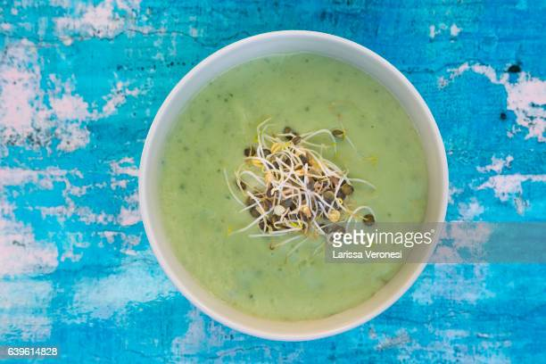 Avocado soup with sprouts on blue surface