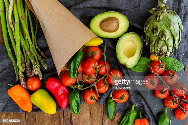 Avocado, tomato, peppers, asparagus and artichoke on wooden table