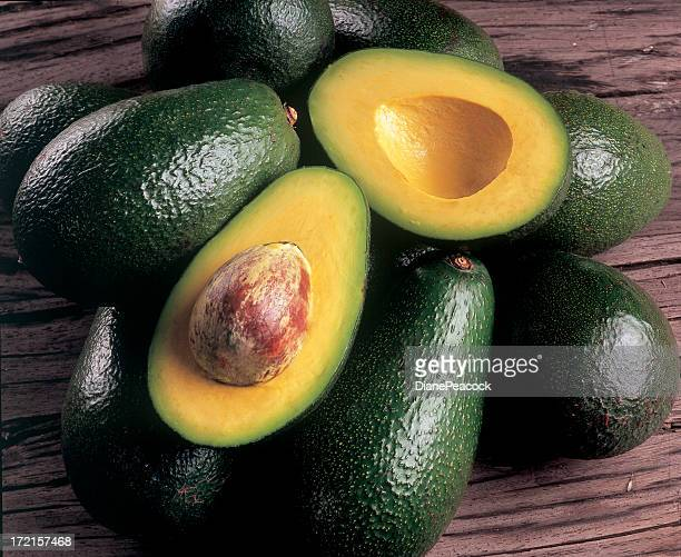 Avocados piled on top of each other with one cut open