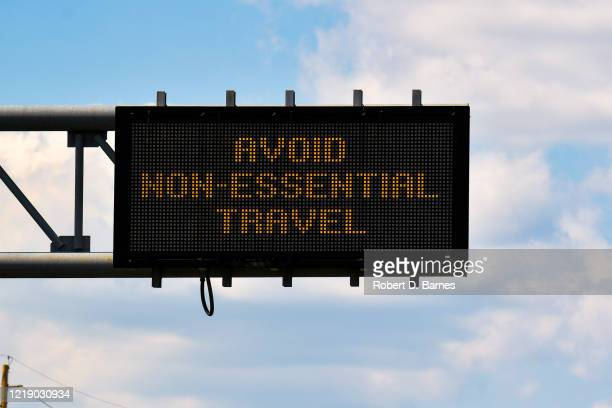 avoid non-essential travel (highway sign) - quedarse en casa frase fotografías e imágenes de stock