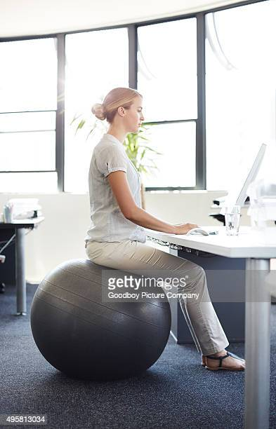 avoiding back pain in the office - fitness ball stock pictures, royalty-free photos & images
