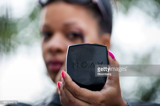 Avon Products Inc sales representative Haizel McIntyre holds a product during an Avon Magic Bus recruiting event in the Bronx borough of New York US...