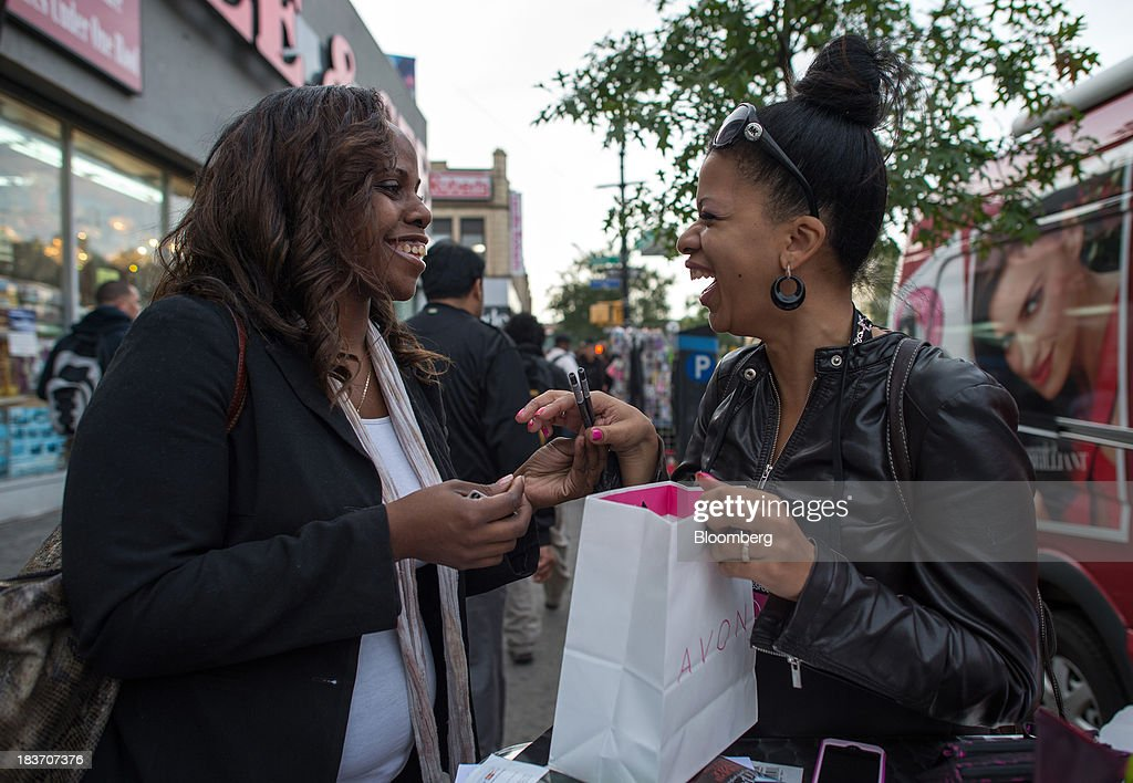 Avon Products Inc. sales representative Haizel McIntyre, right, shows Glory Robinson beauty products during an Avon Magic Bus recruiting event in the Bronx borough of New York, U.S., on Tuesday, Oct. 8, 2013. Beauty and personal-care sales and earnings are expected to exceed those of household products in 2013 with recovering mass-beauty companies like Avon positioned at the top end of 2013 consensus earnings expectations. Photographer: Ron Antonelli/Bloomberg via Getty Images