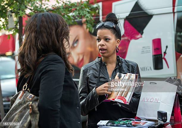 Avon Products Inc sales representative Haizel McIntyre right shows Glory Robinson beauty products inside a brochure during an Avon Magic Bus...